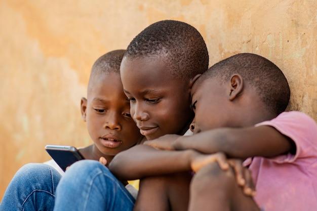 デバイスを見ているクローズアップの子供たち