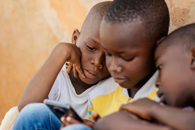 スマートフォンを見ているクローズアップの子供たち