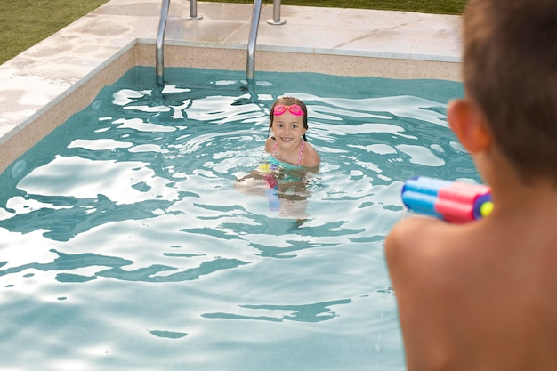 Close up kids playing with water gun