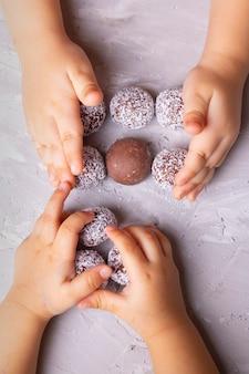 Крупным планом дети делятся трюфелями с орехами и финиками