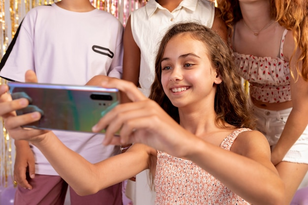Close up kids taking selfie at party