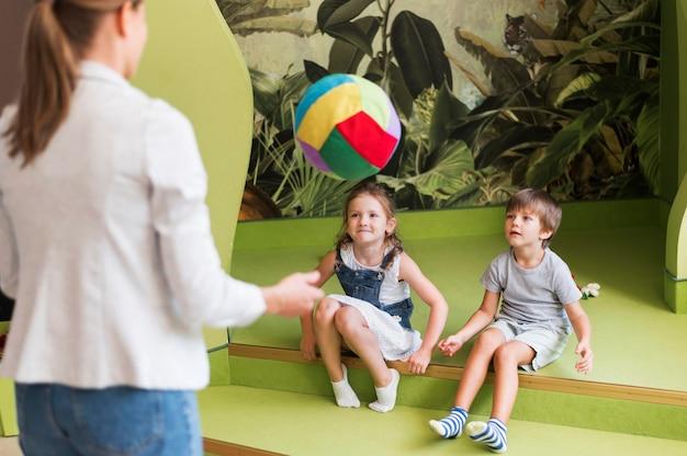 Bambini del primo piano e insegnante che giocano con la palla