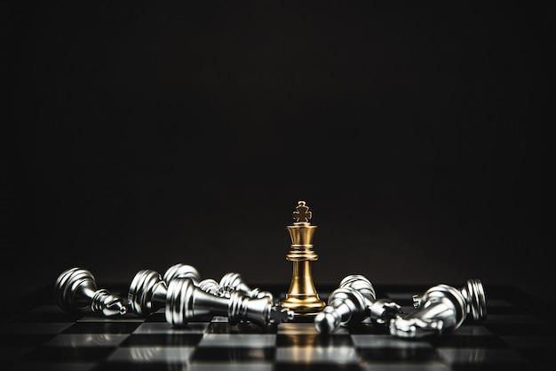 Крупным планом король шахмат, стоящий на шахматной доске с падающими шахматами