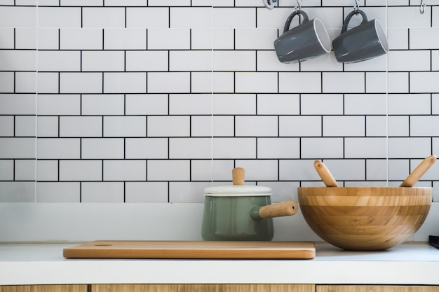 Close-up kitchen room with pot, chopping wood, wooden tub and two ceramic coffee cup put on modern counter