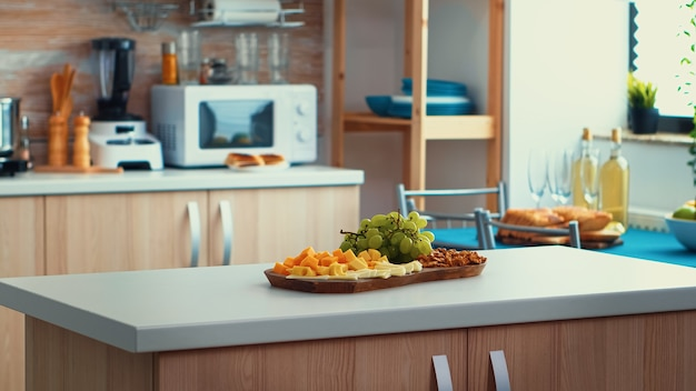 Close up of kitchen table with cheese and grapes on it. open space room interior with daylight, design luxury arhitecture residential decoration with dining table in the middle of the room.