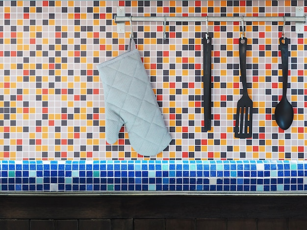 Close up kitchen utensils hanging over colorful mosaic wall tiles.