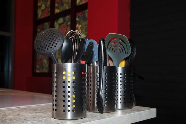 Макро кухонная утварь в контейнерах на фоне таблицы. концепция домашнего декора, инструменты, резиновые аксессуары в контейнере. ресторан, кулинария, кулинарная тематика. концепция общественного питания. копировать пространство
