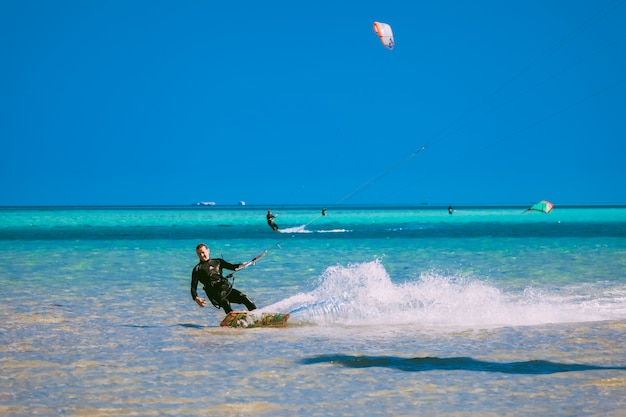 Close-up kitesurfer gliding over the red sea.