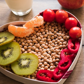 Close-up of kiwi; cherry tomato; orange slices; chickpeas and bell pepper in heart shape bowl