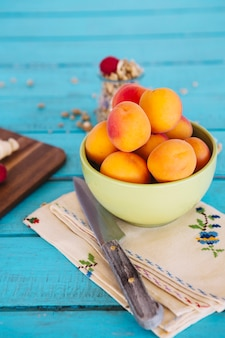 Close-up of knife and fresh peach in bowl on napkin