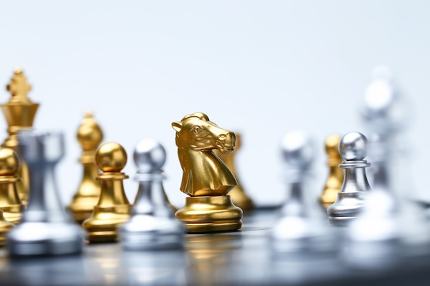 Close up of knight on chess board and chess pieces