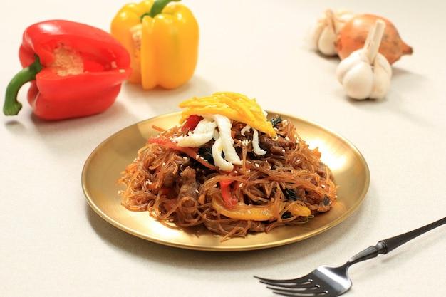 金メッキで野菜と一緒に炒めた韓国の本格的な料理、チャプチェまたは春雨をクローズアップ。毎日または秋夕の日に食べる