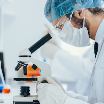 Закройте вверх. лаборант проводит анализирующие пробы в лаборатории.