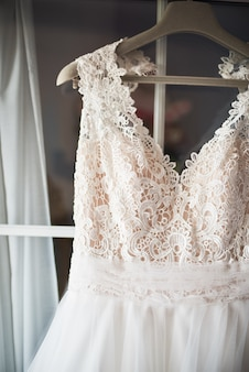 Close-up of a lace wedding dress hanging on the window