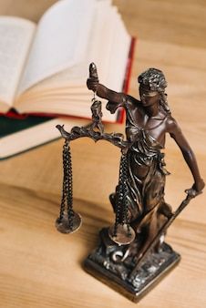 Close-up of lady of justice and law books on wooden desk