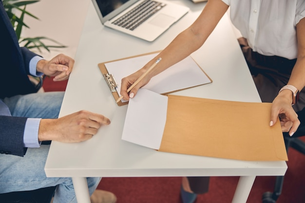 Close up of lady pulling out sheet of paper from office envelope while sitting across the table from man