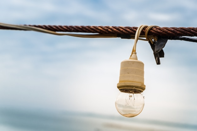 Close up of lamp string light hanging with rusty sling on blue sky background.