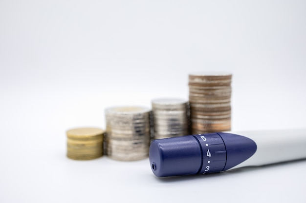 Close up of lancet for check blood sugar level with stack of coins on white