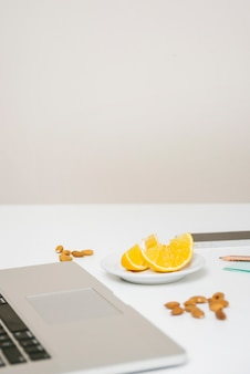 Close-up of laptop; almond; and sweet lime on desk