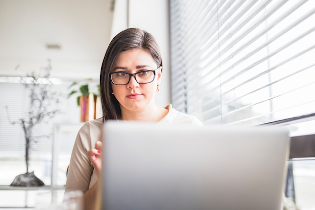 Close-up of laptop in front of young woman with spectacles