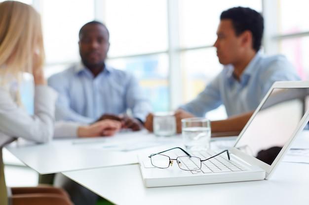 Close-up del computer portatile e occhiali sulla scrivania