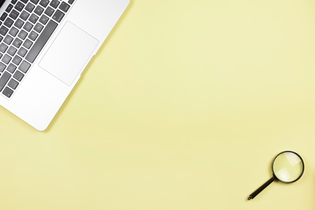 Close-up laptop and magnifying glass on yellow background