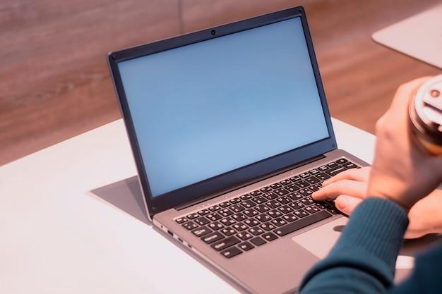 흰색 화면이있는 근접 노트북 모형. 남성 프리랜서가 카페에서 일합니다.