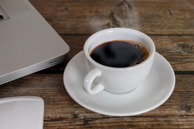 ラップトップを閉じて、木製のテーブルでコーヒーをマウスします。ノートパソコン、マウス、ウッドの背景のコーヒーのコンセプトにブラックコーヒー。