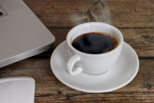 Close up laptop, mouse coffee on wood table. laptop, mouse, black coffee on wood background coffee concept.