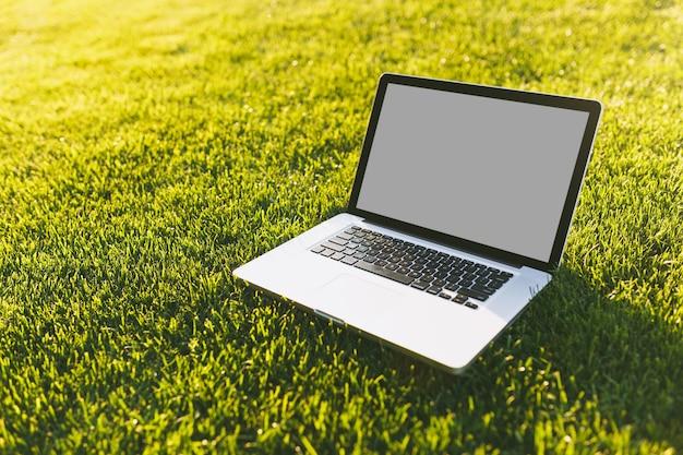 빈 검은색 빈 화면이 있는 랩톱 pc 컴퓨터를 닫고 활기찬 봄 녹색의 신선한 잔디, 야외 자연의 햇살 잔디 초원에 있는 공원 공간을 복사합니다. 모바일 오피스. 프리랜서 비즈니스 개념입니다.