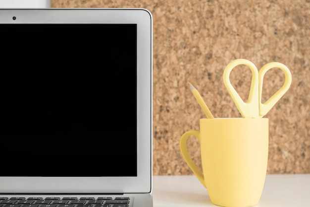 Close-up of laptop screen with scissor and pencil in yellow cup on desk
