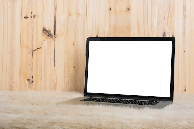 Close-up of laptop on soft fur in front of wooden wall