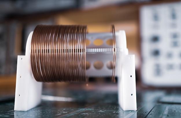 分類された軍事機器の工場の緑色のマイクロ回路上に、銅線を使用した大小のコイルのクローズアップが立っています。超秘密の高周波部品と機器のコンセプト