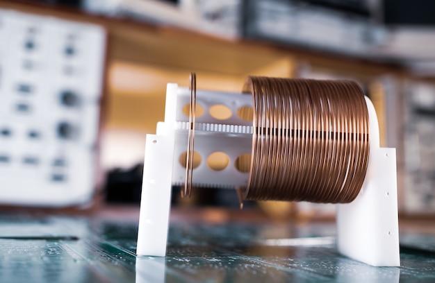 구리선이 있는 크고 작은 코일은 기밀 군사 장비 공장의 녹색 미세 회로에 서 있습니다. 초 비밀 고주파 부품 및 장비 개념