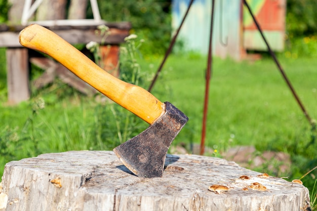 Close-up of a large ax with a wooden handle stuck