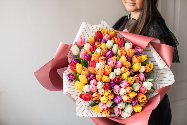 クローズアップ大きな混合チューリップの美しい花束。花の背景と壁紙。花屋のコンセプト。美しいフレッシュカットブーケ。花の配達