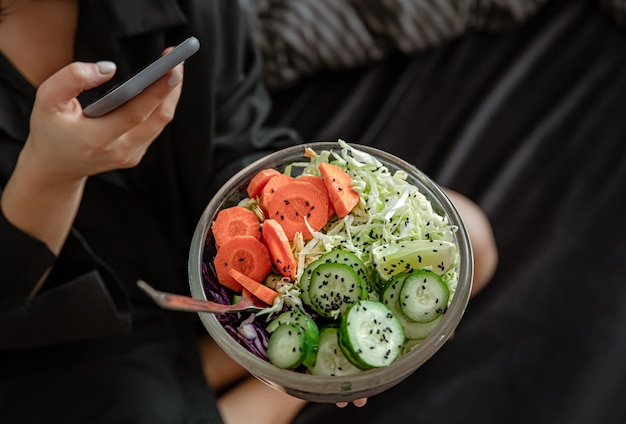 Close up of a large bowl with freshly prepared vegetable salad in female hands.