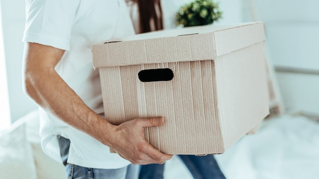 Close up. large cardboard box in the hands of a young man.