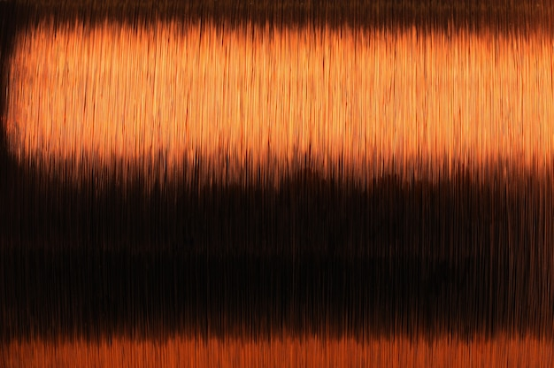 Close-up large coil of thin copper wire in the production of technical parts