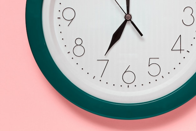 Close up of large office clock on pink