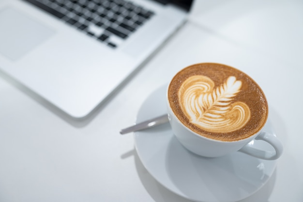 Close up of latte art coffee cup with keyboard of laptop computer