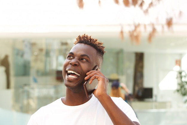 Close up laughing african young man talking on mobile phone and looking away