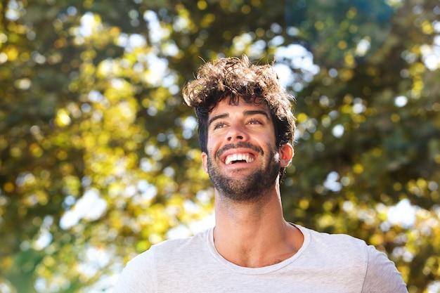 自然の中でひげを持つ笑ってハンサムな男を閉じて