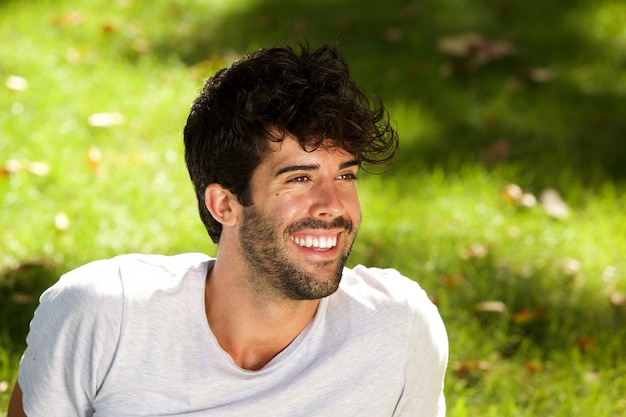 芝生に座っている髭を笑うハンサムな男を閉じて