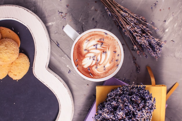 Close up of lavender cappuccino with figure cream in the white cup