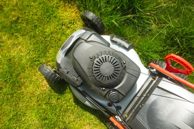 Close up of lawn mower on the grass, read yfor cutting the grass in the garden, gardening concept