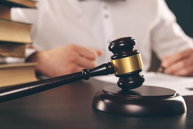 Закройте вверх по бизнесмену юриста, работающему или читающему правовую книгу в офисе на рабочем месте для концепции юрист-консультант.