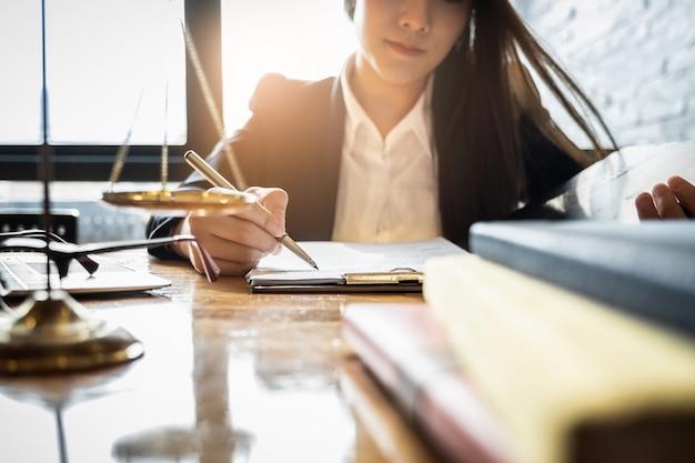 Закройте вверх по закону бизнесмена юриста работая или читая в рабочем месте офиса для концепции юриста консультанта.