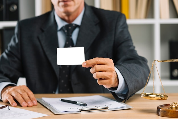 Close-up of lawyer showing white blank card with contract on table