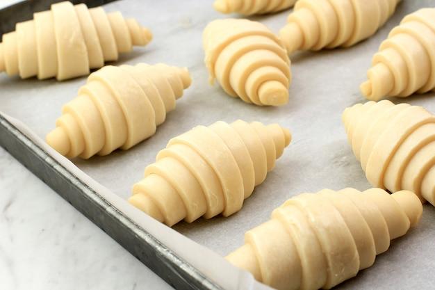 푹신한 발효되지 않은 생 전통 프랑스 크루아상 반죽 롤을 베이킹 트레이와 종이 시트에 겹겹이 쌓아 오븐에서 요리할 준비를 합니다. 버터리, 플래키 페이스트리입니다.